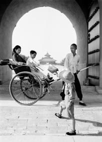 將皮包遞給坐在人力車上的母子。 瓦特爾‧博薩特 中國,約 1937年。 Bag being passed to a mother and child in a rickshaw. Walter Bosshard China, ca. 1937.