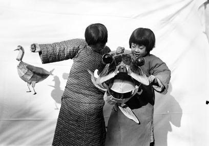 孩子們玩著來自集市的紙偶和風箏。 瓦特爾‧博薩特 中國,約1934年。 Children with a paper toy and kite from a carnival. Walter Bosshard China, ca. 1934.