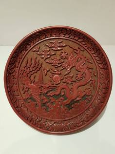 An important Imperial Ming carved polychrome lacquer dragon and phoenix dish Ming Dynasty, Wanli period (1573 – 1620) Eight-character mark dated to the Yiwei Year (1595) D. 21 cm Martin Fung Ltd., Hong Kong