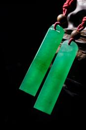 An exceptional pair of jadeite lingguan pendants c. late Qing Dynasty (1644-1911) Approx. H. 62.6 x D. 14.8 mm and H. 62.1 x D. 15.1 mm On Tung Jewellery, Hong Kong