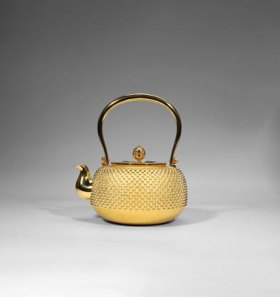 《純⾦ 鏤空花瓣鈕霧霰紋壺》,底款:純金 箱蓋有款 共箱,17 x 16 公分;估價: 280,000至480,000港元; 成交:413,000港元A HAMMERED GOLDEN TEAPOT WITH ARARE EMBOSSMENT, Gold, 17 x 16 cm; Estimate: HK$ 280,000 - 480,000; Sold: HK$ 413,000